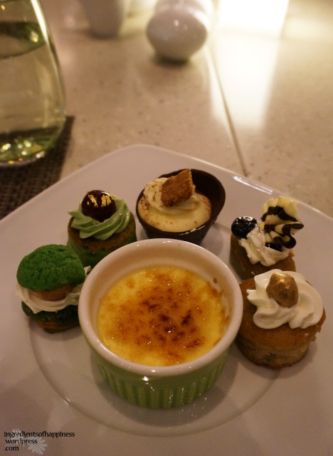 A mini creme brulee surrounded by little puffs and cakes